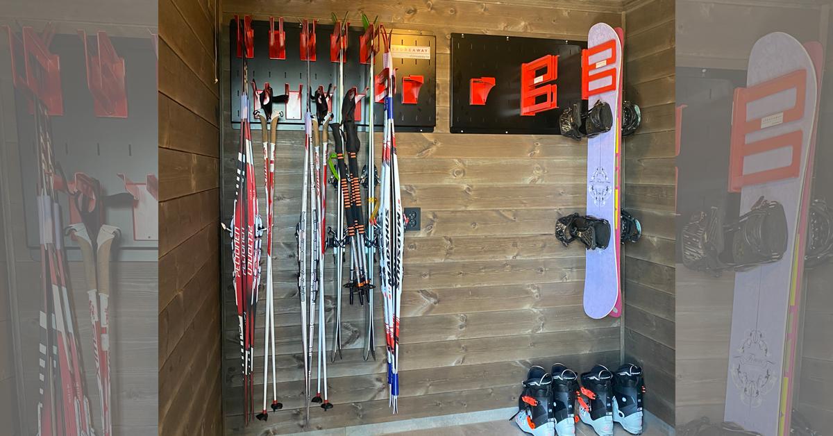 Her har Tonje og Lene fått hengt opp ski, staver og snowboard på Store Away-opphengssystem.